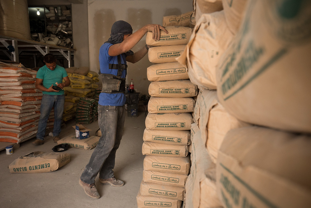 Milton Gomez, 20, carries bags of dry cement mix to laod in the warehouse of Su Ferreteria in Dulce Nombre, Copan, Honduras, March 7, 2018. Central American Medical Outreach located in nearby in Santa Rosa de Copan helps out thousands in Honduras throughout the year with medical assistance, dental, emergency operations, optometry, neurology, and much more. This May will mark their 25th Anniversary.