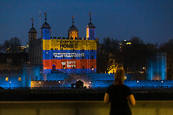 © Licensed to London News Pictures. 09/04/2020. London, UK. A woman stops briefly to look at light projections onto the Tower of London this evening in recognition and appreciation of National Health Service (NHS) and key workers during the ongoing COVID-19 coronavirus epidemic. Photo credit: Vickie Flores/LNP