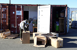 18 November 2020. Care4Calais - Calais, France.<br /> Care4Calais warehouse. A volunteer packs coats and clothes, all cleaned, pre sorted and checked to ensure they are in good condition ready for later distribution to desperate migrant refugees - many of whom have little in the way of warm clothing as winter approaches. <br /> Claire Moseley, founder of the British volunteer run refugee charity Care4Calais works tirelessly to build her foundation  to help migrant refugees as they struggle to survive on the streets of Calais where they are constantly harassed and moved on by authorities. Care4Calais provides meals, clothing, haircuts, charging stations for phones, medical aid, hot drinks, tents, blankets and a wide range of goods and services.<br /> Photo©; Charlie Varley/varleypix.com