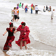 Just a quick dip for two women dressed up as flamenco dancers. Participants dressed up for Folkestone Lions Club Boxing Day Dip.  An annual fancy dress fundraising event, where all sorts of amusing costumes and characters enter the cold sea of the English Channel at Sunny Sands, Folkestone. UK.