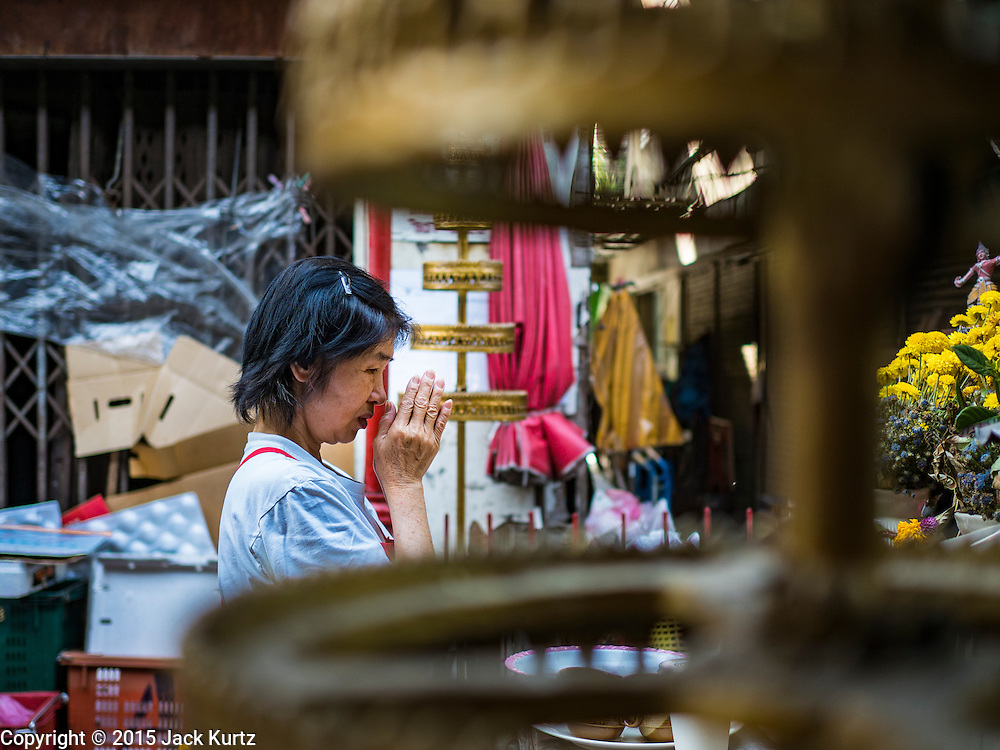 31 DECEMBER 2015 - BANGKOK, THAILAND: A woman prays at a small shrine in Bang Chak Market. The market is supposed to close permanently on Dec 31, 2015. The Bang Chak Market serves the community around Sois 91-97 on Sukhumvit Road in the Bangkok suburbs. About half of the market has been torn down. Bangkok city authorities put up notices in late November that the market would be closed by January 1, 2016 and redevelopment would start shortly after that. Market vendors said condominiums are being built on the land.          PHOTO BY JACK KURTZ