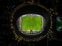 Aerial night view of illuminated Hazza bin Zayed Stadium in Abu Dhabi, UAE.