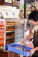 Woman loading a warmer with freshly baked egg tarts in Macau.