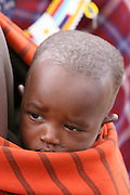 Africa, Tanzania, Maasai an ethnic group of semi-nomadic people baby carried on back on mother