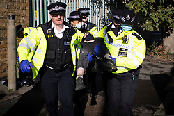 © Licensed to London News Pictures. 04/10/2021. London, UK. An arrested activist from Insulate Britain is carried to a waiting police van at the entrance to the Blackwall tunnel after the group blocked the tunnel earlier this morning. Insulate Britain have successfully blocked various roads around the capital over a number of weeks, resulting in a court injunction banning them from going near the M25 motorway.  Photo credit: George Cracknell Wright/LNP