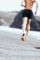 Rear view of man running on sandy beach