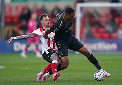 Lincoln City's Chris Maguire (left) challenges Charlton Athletic's Akin Famewo during the Sky Bet League One match at the LNER Stadium, Lincoln. Picture date: Saturday October 16, 2021.