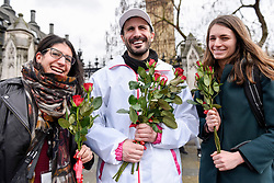 "© Licensed to London News Pictures. 08/03/2017. London, UK. Women receive roses.  A flashmob takes place in Parliament Square as part of International Women's Day.  Apparently backed by the Russian government, a giant balloon is unsuccessfully inflated bearing the text ""From Russia With Love"" and ""#makehersmile"" with organisers handing out roses to unsuspecting female passers by. Photo credit : Stephen Chung/LNP"