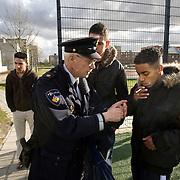 Nederland Rotterdam 3 maart 2008 20080303.Wijkagent biedt vuurtje aan aan jongere voor het aansteken sigaret naast het Cruijff Court in moordwijk probleemwijk Kralinger Esch waar recent 3 moorden werden gepleegd..Foto David Rozing