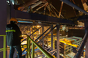 A dock worker standing on a gantry crane looks down onto CMA CGM SAs Benjamin Franklin container ship at the Xiamen Songyu Container Terminal at night in Xiamen, China, on Saturday, Jan. 30, 2016. The Benjamin Franklin is the largest container ship ever to have docked at a U.S. port.
