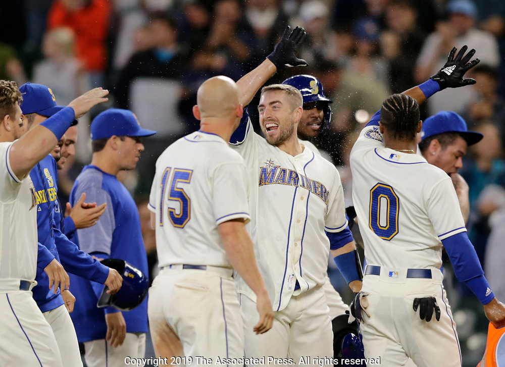 Seattle Mariners players surround Tom Murphy after a bases loaded walk from Chicago White Sox relief pitcher Jose Ruiz in the bottom of the ninth inning to win 11-10 a baseball game, Sunday, Sept. 15, 2019, in Seattle. (AP Photo/John Froschauer)