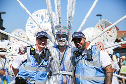 © Licensed to London News Pictures. 26/08/2019. London, UK. Police officers pose with a dancers on the second day of Notting Hill Carnival in west London. Thousands of revellers take part in Notting Hill Carnival, Europe's largest street party and a celebration of Caribbean traditions and the capital's cultural diversity. Photo credit: Dinendra Haria/LNP