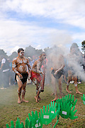 Aboriginal dancers emerge from smoke during traditional cleansing ceremony. National Sorry Day celebration, Perth, Western Australia