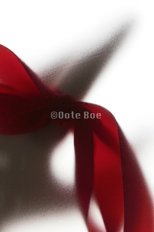 hand with large red ribbon on one if its fingers behind frosted glass