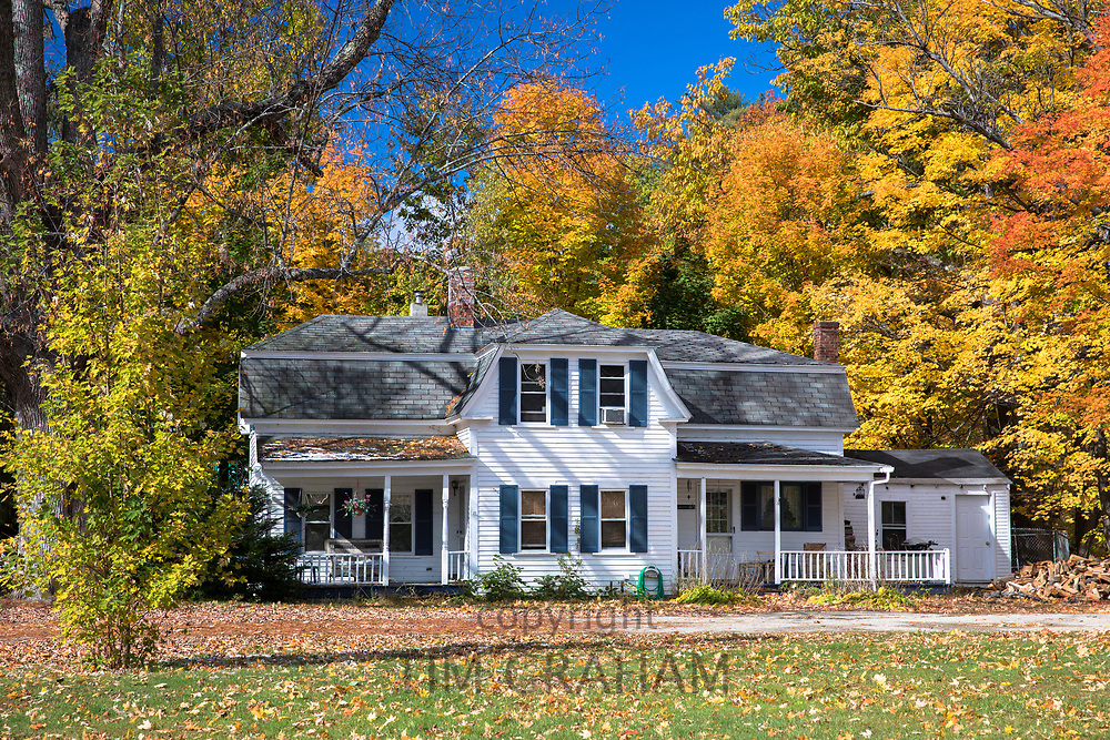 Neat traditional, typical wooden white clapboard house surrounded by Fall foliage, in Conway, New Hampshire, USA