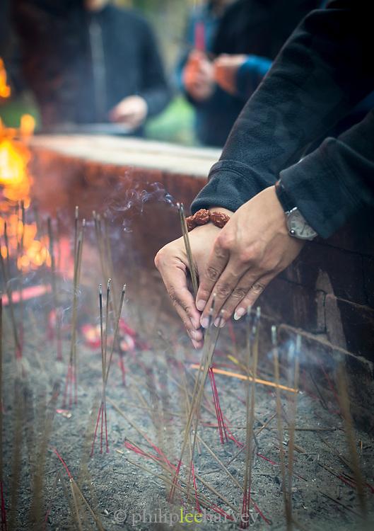 Close-up of the hands of a female worshiper lighting incense sticks, Lingyin Buddhist temple, Hangzhou, Zhejiang Province, China