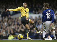 Photo: Aidan Ellis.<br /> Everton v Arsenal. The Barclays Premiership. 21/01/2006.<br /> Arsenal's Thierry Henry miss hits a shot as Everton's Phil Neville looks on
