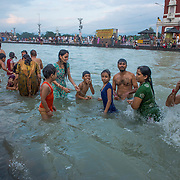 Families gather to bathe in the sacred, purifying waters of the Ganges River at Har Ki Pauri ghat in Haridwar, Uttarakhand, India.