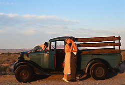 young boy covering his eyes while a couple kisses in front of an old truck