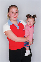Young mother holding baby daughter smiling,