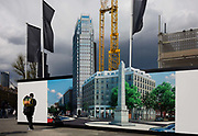 A pedestrian walks past a hoarding showing the future skyscraper being built by housing developer Barratt at Blackfriars Circus at the southern end of Blackfriars Bridge Road, south London borough of Southwark. In the foreground is the image of the obelisk that occupies the junction, was built in 1771. Local opposition groups object to this new landmark, one of many futuristic buildings going up to dominate the south London landscape.  Typically, property in these developments are owned by foreign non-residents.