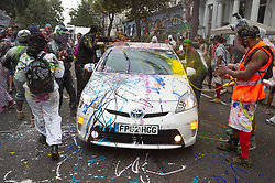 © Licensed to London News Pictures. 26/08/2018. London, UK. Revellers paint a car that gets caught up during Jouvert, a paint fight that officially marks the start of the Notting Hill carnival. The two day event is the second largest street festival in the world after the Rio Carnival in Brazil, attracting over 1 million people to the streets of West London. Photo credit: Ray Tang/LNP
