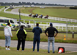 © Licensed to London News Pictures. 04/07/2020. Epsom, UK. A small crowd watch from outside a security fence as the first outing of the Derby Day race meeting takes place as the riders in The Investec Woodcote EBF Stakes pass by. Today's race meeting is being held behind closed doors due to the coronavirus lockdown rules. Seven races are being held in one day including The Oaks, with The Derby being run at 4:55pm. Photo credit: Peter Macdiarmid/LNP