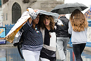Two women shelter under a rain poncho on Tower Bridge during rain and wet weather in London, England on August 10, 2018