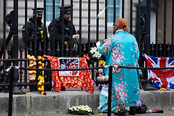 © Licensed to London News Pictures.10/04/2021. London, UK. Police talk to a woman as a worker removes flags and floral tributes that have been left outside Buckingham Palace. Yesterday Buckingham Palace announced that Prince Philip The Duke of Edinburgh passed away in the morning at Windsor Castle . Photo credit: George Cracknell Wright/LNP