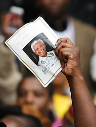 Mandela Memorial Service.<br /> 60813444 <br /> A person holds a poster of Nelson Mandela before the memorial service for the former South African president at the FNB Stadium in Soweto near Johannesburg, South Africa, Tuesday, 10th December 2013. Picture by  imago / i-Images<br /> <br /> UK ONLY