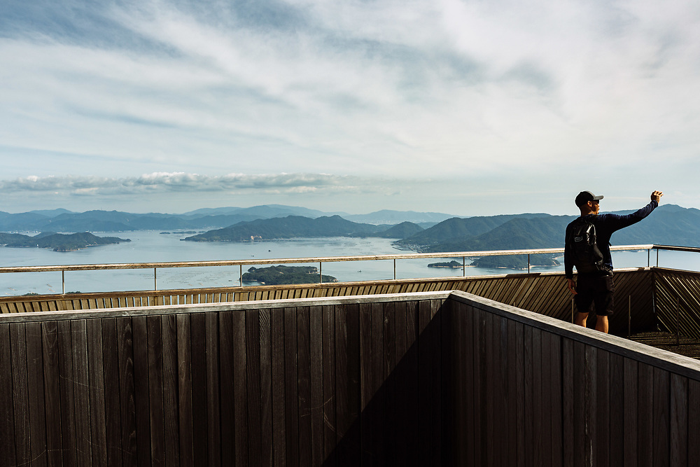 A man poses for a selfie with a view of the Hiroshima Bay and the city of Hiroshima, from the Mount Misen Observatory on Itsukushima Island (Miyajima), Hiroshima prefecture, Japan.