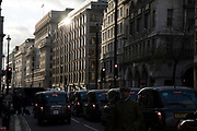 Street scene on Piccadilly in central London as the sun sets and reflects on buildings and black taxi cabs pass in the low light in London, England, United Kingdom.