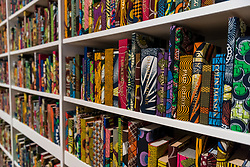 "© Licensed to London News Pictures. 08/04/2019. LONDON, UK.  Detail of ""The British Library"", 2014, by British-Nigerian artist Yinka Shonibare.  The artwork has just been acquired by Tate Modern.  Comprising 6,328 books, covered in wax fabric and gold foil, 2,700 books have the names of first or second generation immigrants to Britain on the spine.  Photo credit: Stephen Chung/LNP"