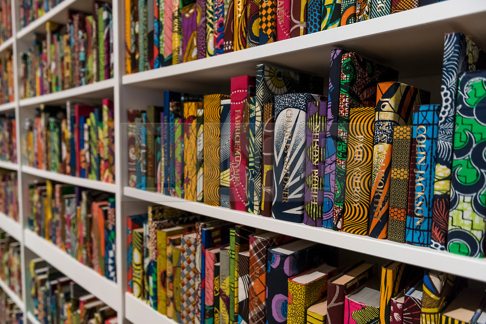 """© Licensed to London News Pictures. 08/04/2019. LONDON, UK.  Detail of """"The British Library"""", 2014, by British-Nigerian artist Yinka Shonibare.  The artwork has just been acquired by Tate Modern.  Comprising 6,328 books, covered in wax fabric and gold foil, 2,700 books have the names of first or second generation immigrants to Britain on the spine.  Photo credit: Stephen Chung/LNP"""
