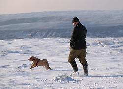 © Licensed to London News Pictures. <br /> 27/12/2014. <br /> <br /> Castleton, United Kingdom.<br /> <br /> A man walks his dog across a field on the North Yorkshire Moors near Castleton after overnight snowfall caused disruption in some parts of the country.<br /> <br /> Photo credit : Ian Forsyth/LNP