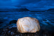 A smooth boulder among icebergs, calved by nearby Hansbreen, on a beach in Hornsund, Svalbard.