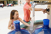 HOT SPRINGS, AR – JUNE 29, 2013: Aspen Ramey (left) fills a water bottle with warm spring water near historic Bathhouse Row.