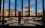 Viewed through the decorative iron grate of a window, the buildings along the Grand Canal reflect the late afternoon light on a summer day in Venice, Italy