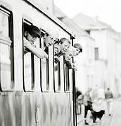 A group of friend lean from windows of a train carriage near Bad Doberan, northern Germany