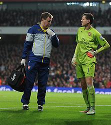 Arsenal's Wojciech Szczesny hold his side as he gets taken off the pitch. - Photo mandatory by-line: Alex James/JMP - Mobile: 07966 386802 - 22/11/2014 - Sport - Football - London - Emirates Stadium - Arsenal v Manchester United - Barclays Premier League