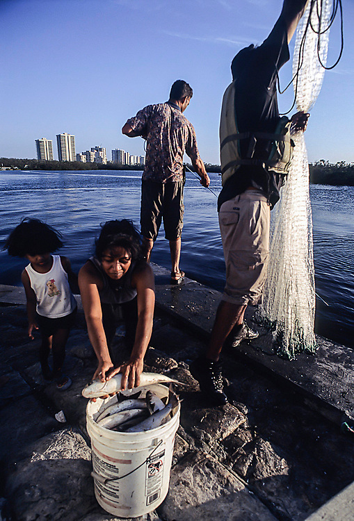 A family of immigrants fishes for mullet in the Lake Worth Lagoon in Singer Island, Florida, United States