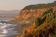 Sunset light on the coastal bluffs and waves on sand beach at Leffingwell Landing, Cambria, California