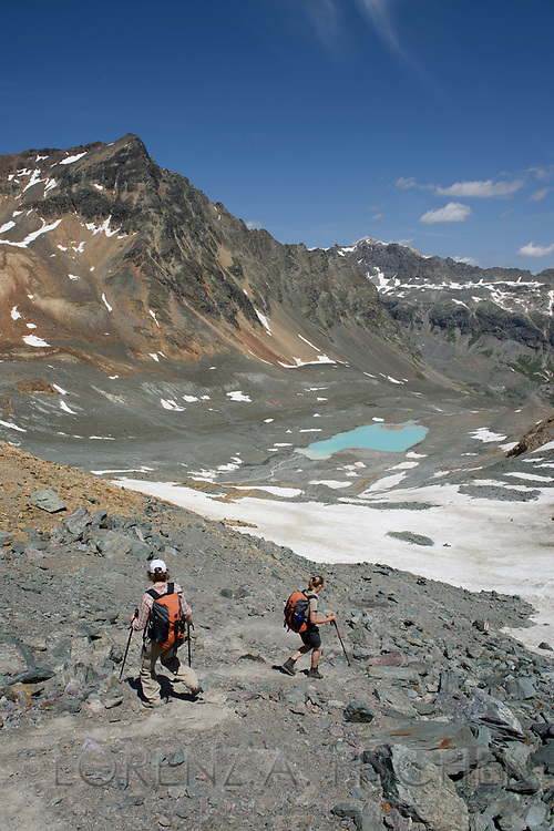 Two women are hiking down from the Fuorcla d'Agnel into the upper Val Bever with a glacier lake on a nice summer day in July with the Crasta Jenatsch in sight, Engadin, Grisons, Switzerland