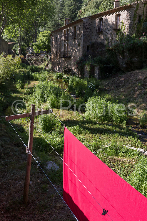 A pink sheet dries on a communal village washing line in morning sunlight, on 26th May, 2017, in Termes, Languedoc-Rousillon, south of France.