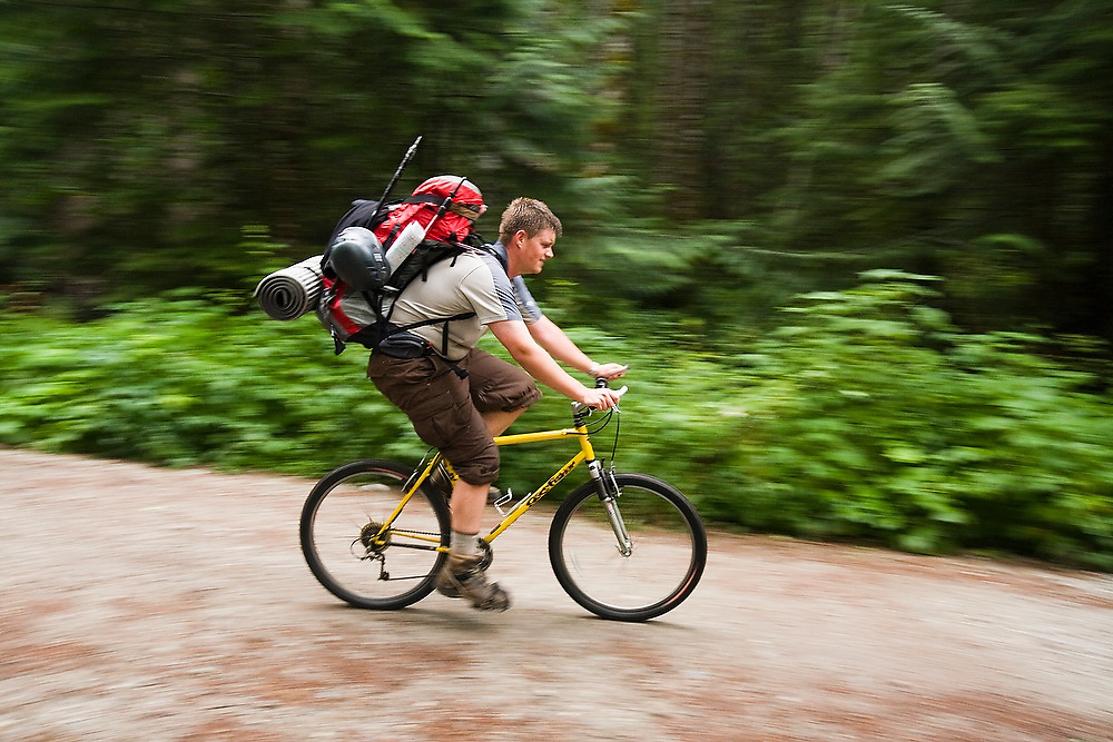 Brian Doehle bikes with his climbing gear up the closed road to the trailhead for the North Fork Sauk River Trail in Glacier Peak Wilderness, Washington, on the way to Glacier Peak.
