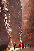 Tourists walk down Al Siq, the slot canyon entrance to Petra, Jordan.