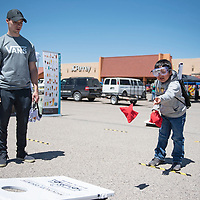 Roshaun Yazzie, 8, plays cornhole while wearing Fatal Vision simulation goggles while Joshua Johnson, a volunteer of the event watches during McKinley County DWI awareness day Saturday, June 8, outside Rio West Mall in Gallup.