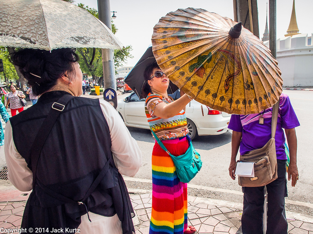 15 OCTOBER 2014 - BANGKOK, THAILAND:  A vendor tries to sell souvenir umbrellas to tourists near the Grand Palace in Bangkok. The number of tourists arriving in Thailand in July fell 10.9 per cent from a year earlier, according to data from the Department of Tourism. The drop in arrivals is being blamed on continued uncertainty about Thailand's political situation. The tourist sector accounts for about 10 per cent of the Thai economy and suffered its biggest drop in visitors in June - the first full month after the army took power on May 22. Arrivals for the year to date are down 10.7% over the same period last year.   PHOTO BY JACK KURTZ