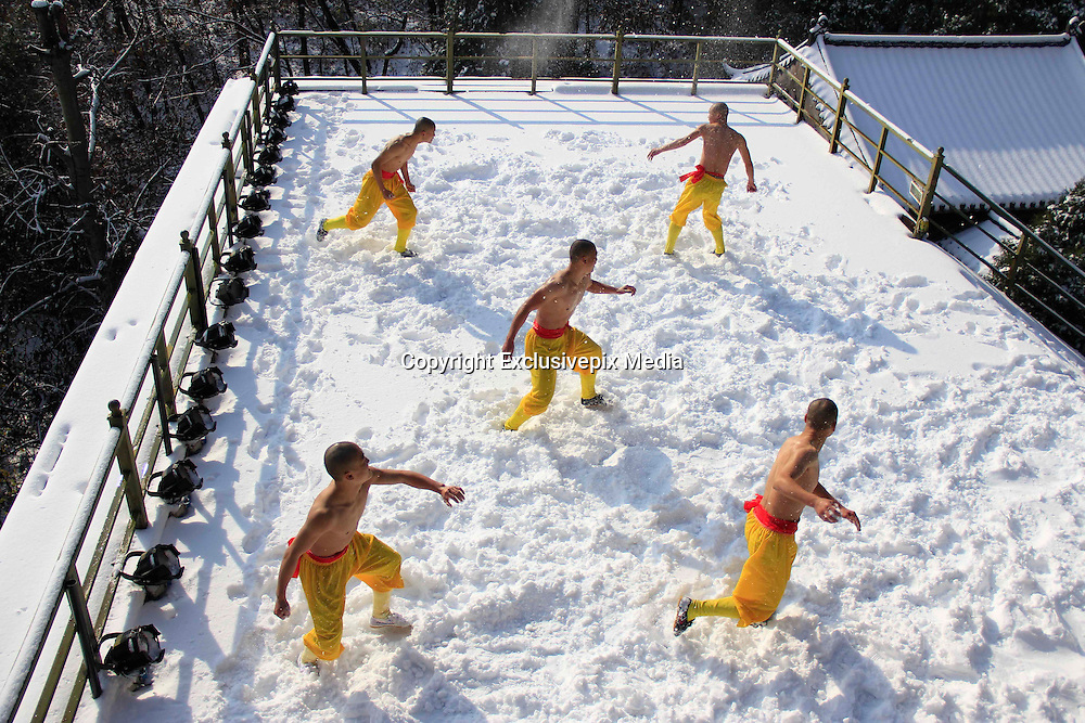 """ZHENGZHOU, CHINA - NOVEMBER 25: (CHINA OUT)<br /> <br /> Monks Exercise In Snow <br /> <br />  Five Buddhist monks exercise in snow while going shirtless in Songshan Mountain scenic resort of Dengfeng County on November 25, 2015 in Zhengzhou, Henan Province of China. They exercise for the performance on \""""Shaolin Zen Music Ritual\"""" at the end of the year. ©Exclusivepix Media"""