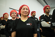 "SanDisk employee Tracy Nguyen listens to food packing instructions during the Stop Hunger Now Foundation's ""Mayday, Mayday"" food-packing event at SanDisk Corporation in Milpitas, California, on May 13, 2014. (Stan Olszewski/SOSKIphoto)"